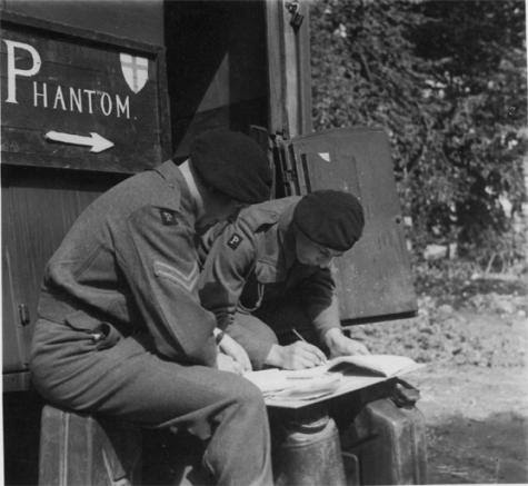 Two Phantom soldiers consulting a map and drafting a mission report. Note the 'P' patches on their right shoulders identifying the GHQ Liaison Regiment
