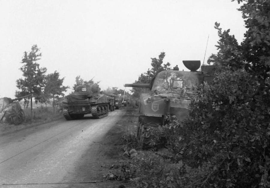 A knocked-out British tank being passed by others on Hell's Highway. Note how narrow the road is.