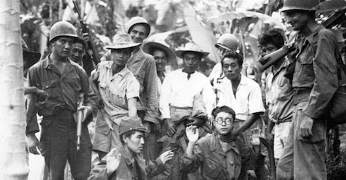 Filipino guerillas and American soldiers with captured Japanese troops